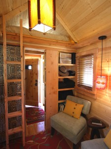 Interior of a small home with a loft bed by Jay Shafer